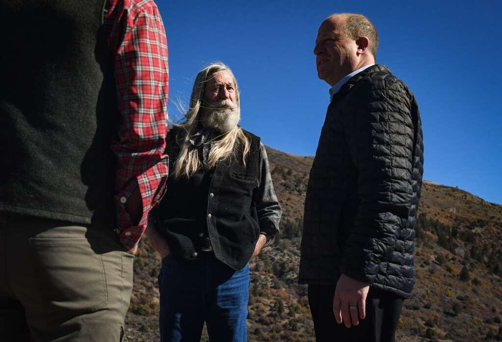 Colorado Gov. Jared Polis talks with Garfield County Commissioner John Martin before the start of Wednesday's press conference at Sweetwater Lake. |Chelsea Self/Post Independent