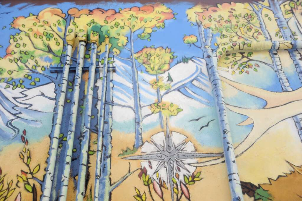 Greg Effinger turned a sketch by Ben Rock into a mural as part of Steamboat Creates behind Straightline Sports on 8th street between Lincoln and Oak. He turned pipes running up the side of the building into trees, blending them into the painting. (Photo by Shelby Reardon)