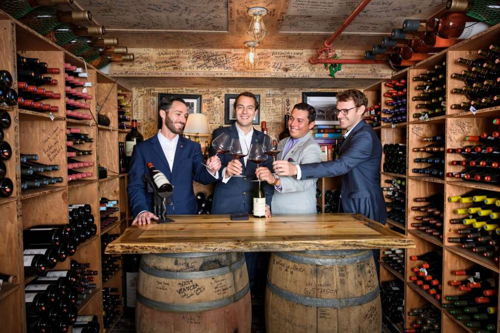 Jesse Libby, Chris Dunaway, Oscar Fernandez and Jacob Johnson cheers in The Little Nell wine cellar.