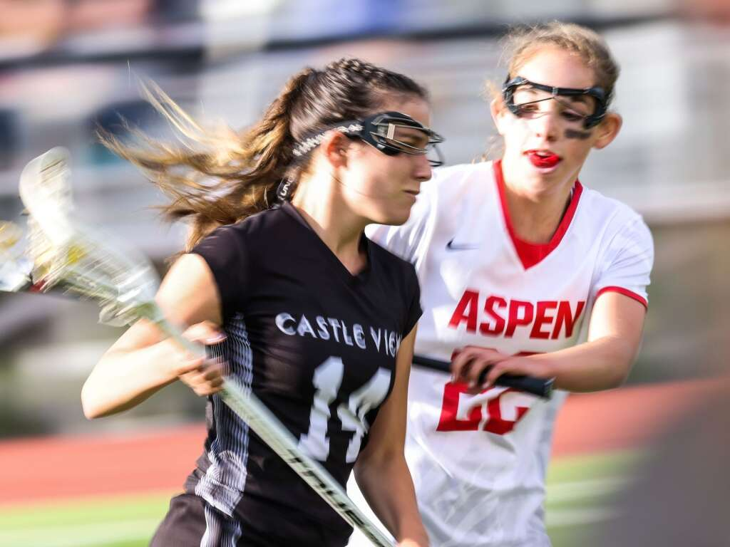Aspen High School's Michaela Kenny, right, defends in the girls lacrosse game against Castle View in the Class 4A state quarterfinals on Saturday, June 19, 2021, on the AHS turf. The Sabercats won, 10-9. Photo by Austin Colbert/The Aspen Times.