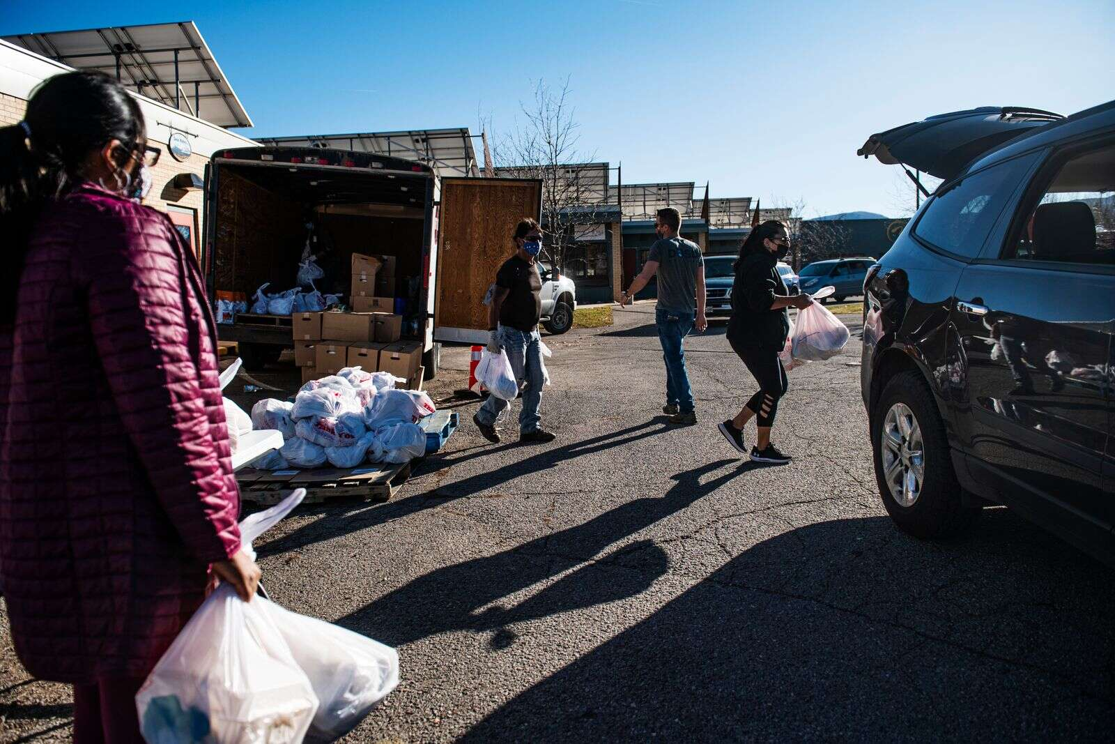 Lift-Up staff and volunteers carry bags of food to familyu2019s vehicles during a distribution at Third Street Center in Carbondale on Monday, Nov. 16, 2020. (Kelsey Brunner/The Aspen Times)