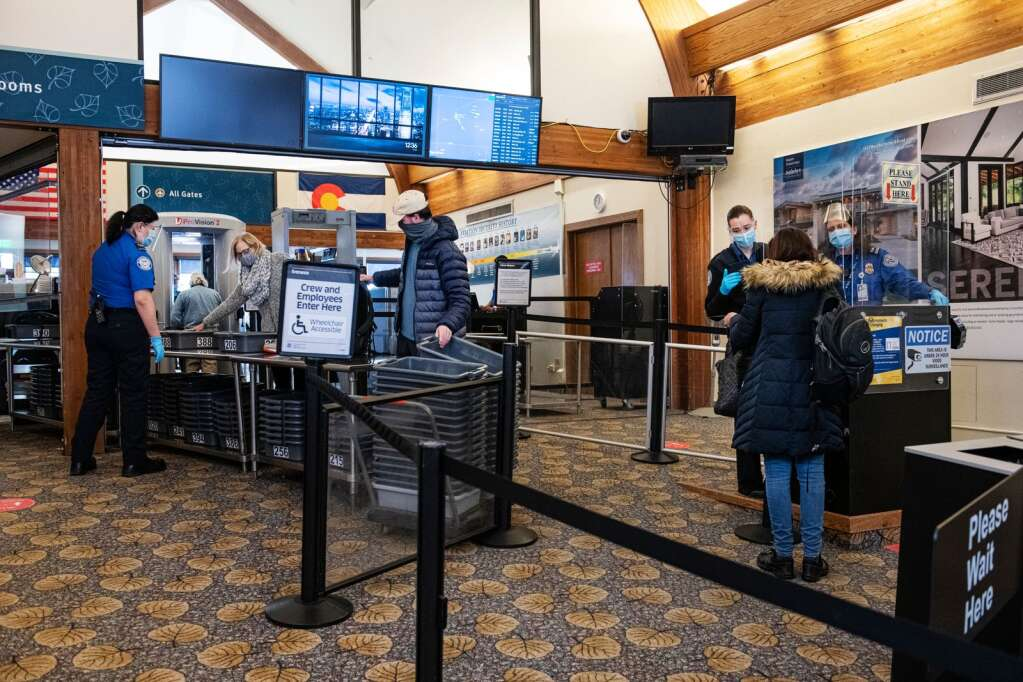 TSA agents assist passengers at the Aspen/Pitkin County Airport on Tuesday, Dec. 29, 2020. (Kelsey Brunner/The Aspen Times)