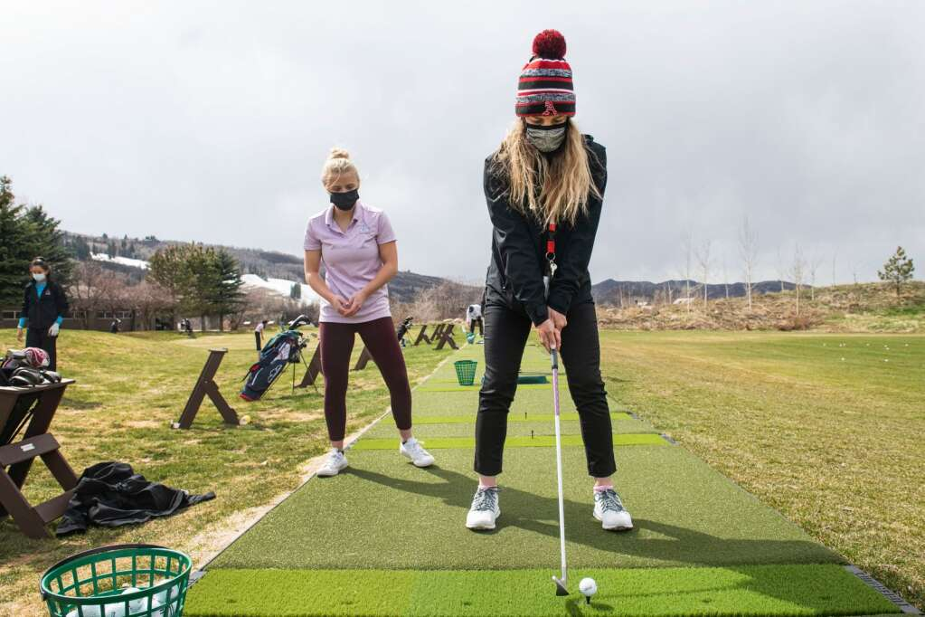 Aspen High School's girls golf team head coach Shannon Worth helps freshman Eva Thirion with her grip and swing during practice on the driving range at Aspen Golf Club on Wednesday, April 21, 2021. (Kelsey Brunner/The Aspen Times)