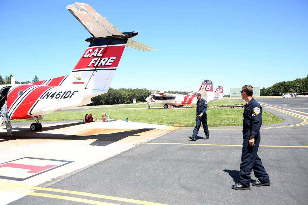 Cal Fire Air Tactical Ground Support Captain Sean Ryan and Battalion Chief David Krussow walk towards the Cal Fire Beechcraft King Air airplane that they have been training in for the past two weeks at the Grass Valley Interagency Air Attack Base. | Photo: Elias Funez
