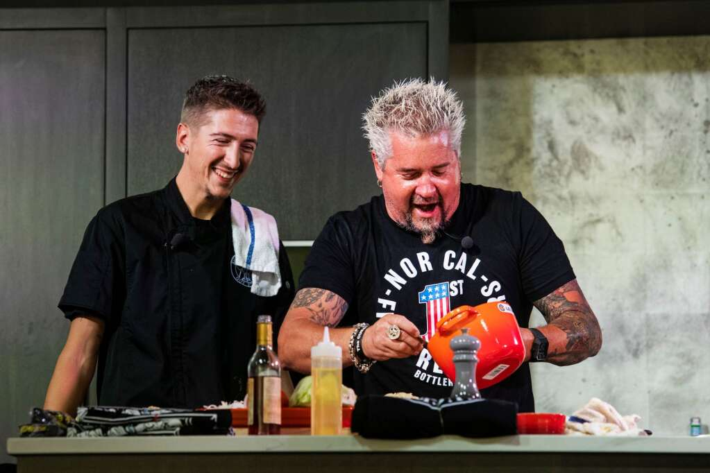 Guy Fieri and his son Hunter Fieri spoon cashew vegan cheese onto his vegan burger during a morning seminar at the Food & Wine Classic in Aspen on Saturday, Sept. 11, 2021. (Kelsey Brunner/The Aspen Times)