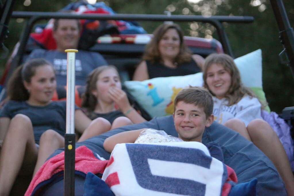 Members of the Barber Family enjoy a bag of Onyx Theater popcorn while waiting for Saturday night's movie to start. Movies start at sunset and guests are asked to arrive no later that 8:30 p.m.   Photo: Elias Funez