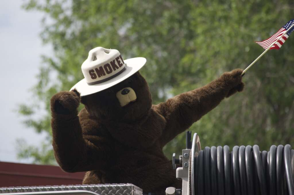 Smokey the Bear poses with an American Flag at Craig's Fourth of July parade, held July 5, 2021, marched down Victory Way Monday morning. | Cuyler Meade / Craig Press