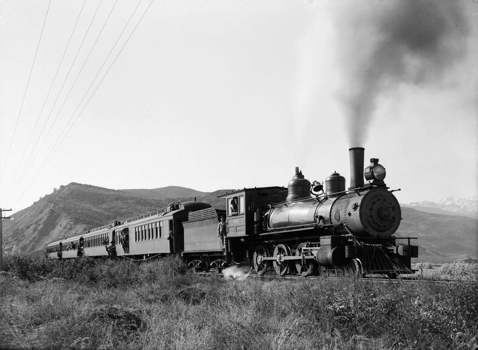 One b/w glass-plate negative of engine 32, Colorado Midland Railroad passenger train.  Several people are leaning out of the passenger cars.  Power lines are visible on the left side of the photo.  The Shale Bluffs are in the background. Circa 1900. Cozy Point Area.