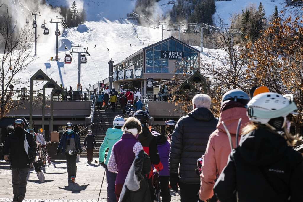 A line of skiers snakes to the road from the Silver Queen Gondola at the base of Aspen Mountain on Thursday, Dec. 3, 2020. (Kelsey Brunner/The Aspen Times)
