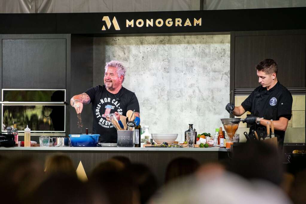Guy Fieri adds seasoning to his vegan dish with his son Hunter Fieri at the Food & Wine Classic in Aspen on Saturday, Sept. 11, 2021. (Kelsey Brunner/The Aspen Times)