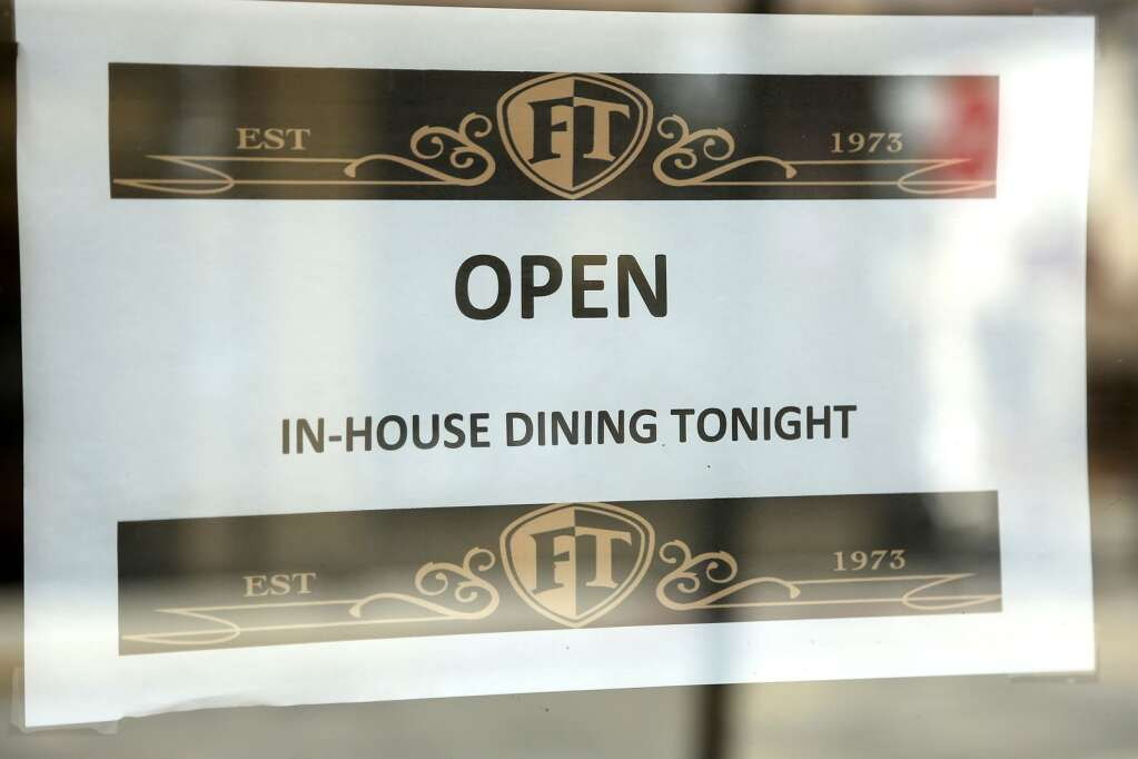 A sign posted to the front doors of Friar Tuck's in Nevada City lets folks know that they plan for in-house dining Wednesday evening despite coronavirus guideline restrictions. | Photo: Elias Funez