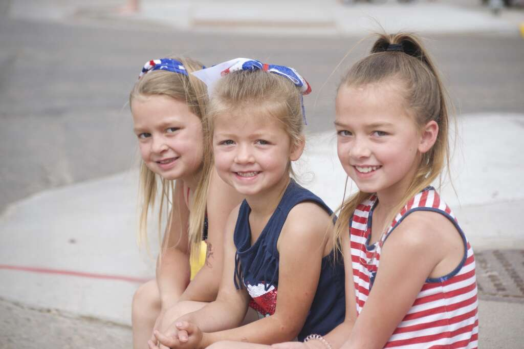 From left, Audrey, Morgan and Charlotte Kaughey pose for a photo as they watch Craig's Fourth of July parade, held July 5, 2021, marched down Victory Way Monday morning. | Cuyler Meade / Craig Press