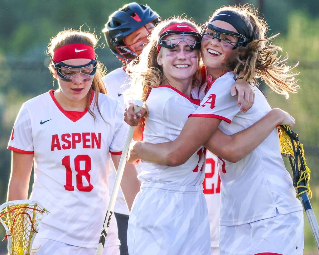 Aspen High School girls lacrosse players Kylie Kenny, right, and Georgia Hollander hug while walking off the field after a loss to Castle View in the Class 4A state quarterfinals on Saturday, June 19, 2021, on the AHS turf. The Sabercats won, 10-9. Photo by Austin Colbert/The Aspen Times.