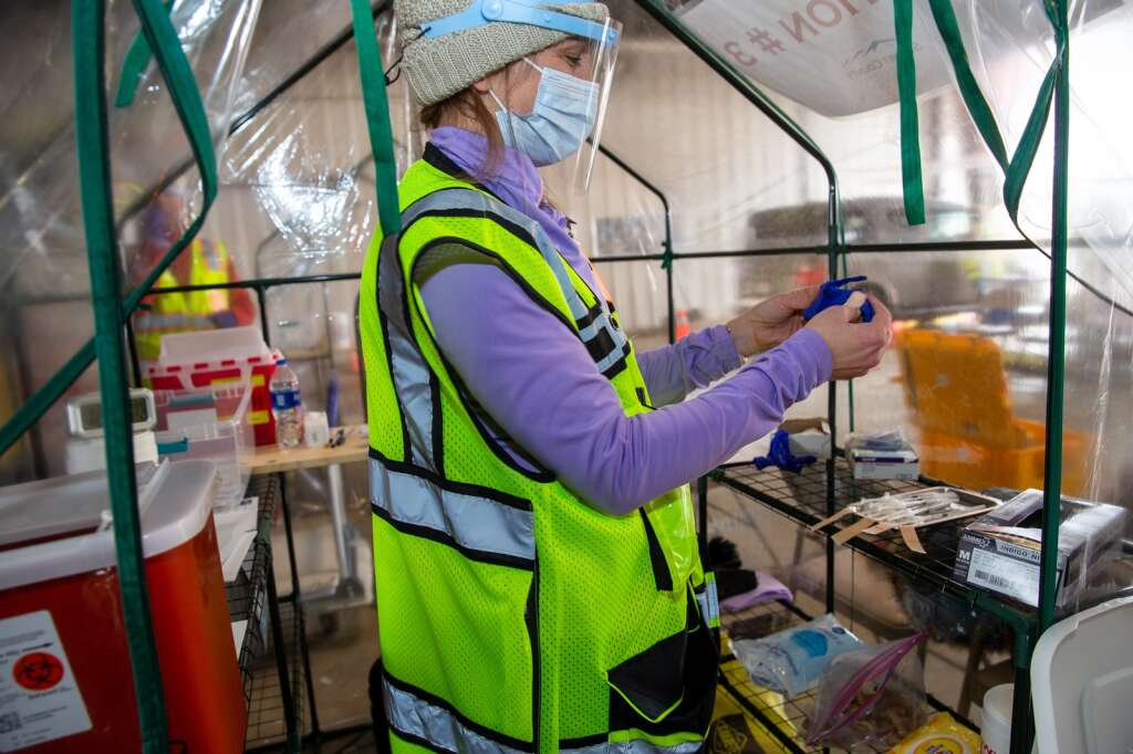 Summit County Public Health volunteer Amanda Merriman puts on a fresh pair of gloves to administer COVID-19 vaccines on Saturday, Feb. 13, 2021 at the bus depot in Frisco, Colo. Photo by Liz Copan / Studio Copan