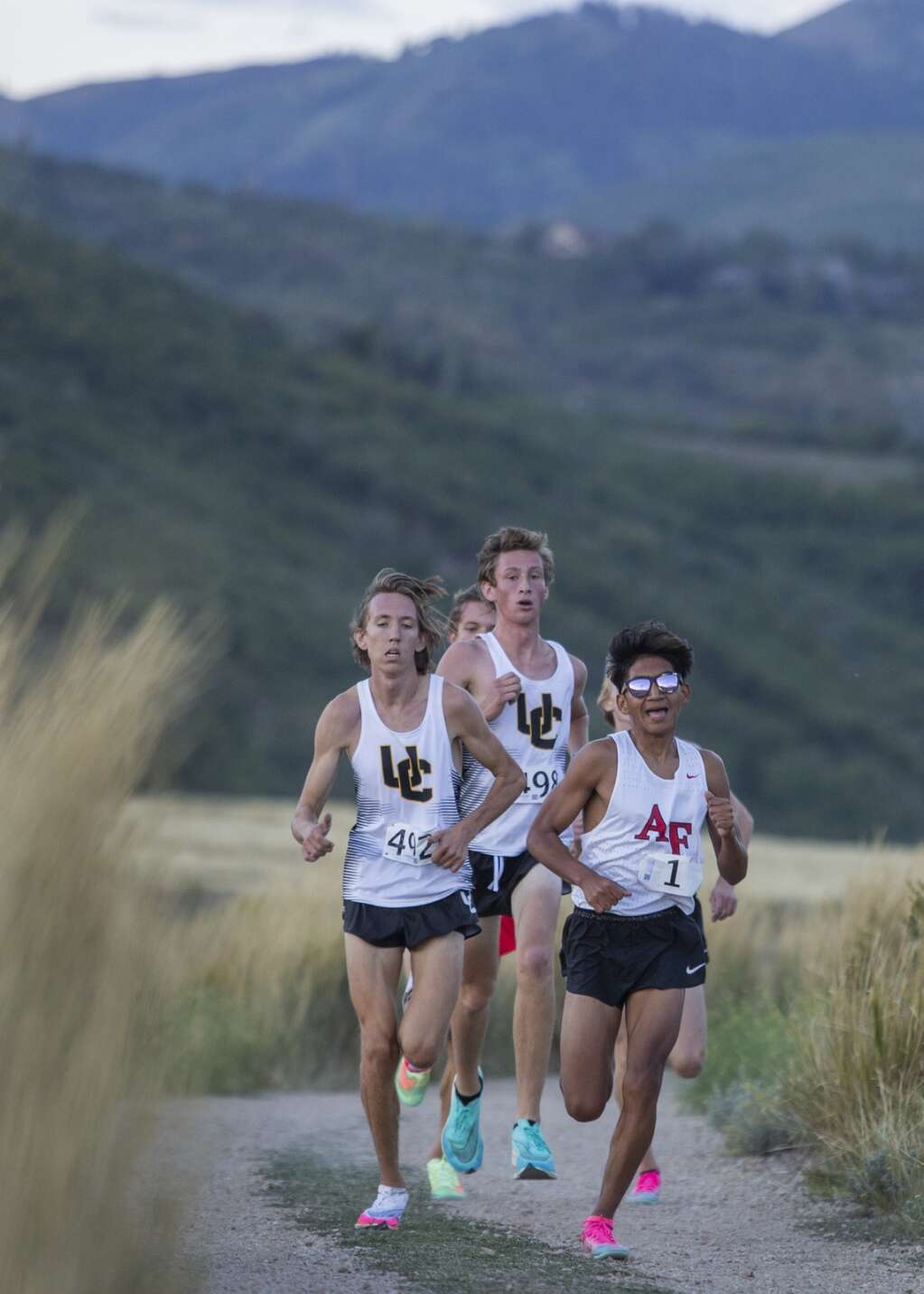 Boys varsity runners pick up the pace as they approach the final stretch of the course during the Park City High School invitational cross country meet in Round Valley Friday evening, Sept. 10, 2021. (Tanzi Propst/Park Record)