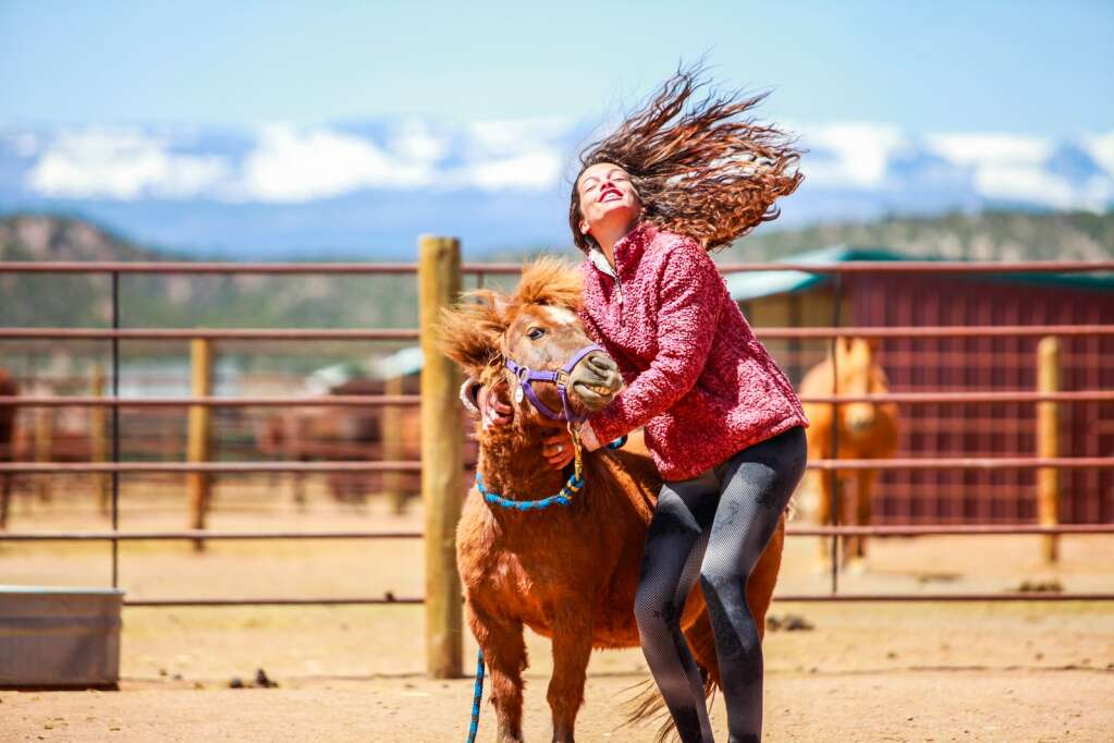 Volunteer Taylor Corey unsuppectingly throws her hair back while giving Racey stracthes at the Mountain Valley Horse Rescue May 2020 in McCoy.