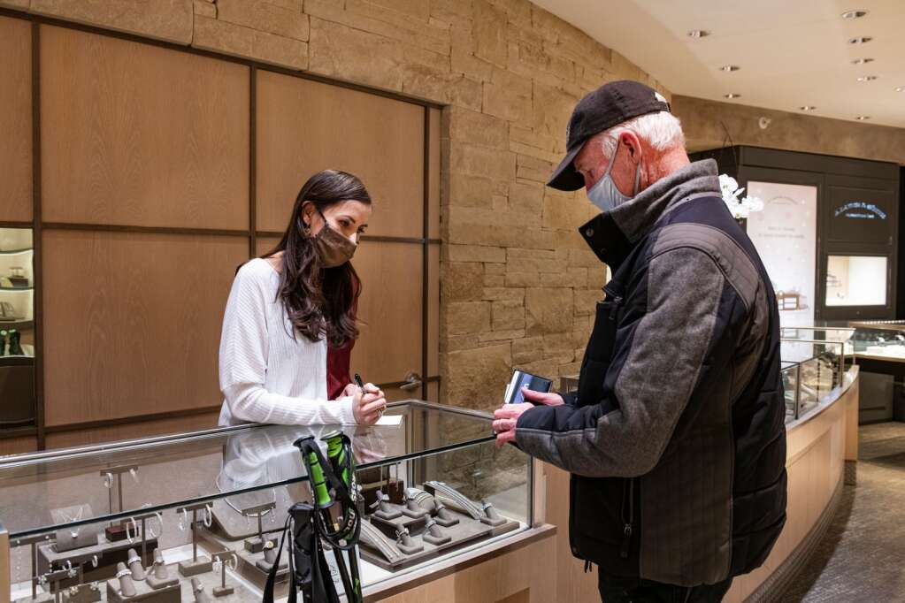 "Lorena Rojas transcribes information from Rick Wark as he purchases two $200 gift certificates to restaurants in Aspen on Wednesday, Jan. 20, 2021. ""I want to support the community,"" said Wark. ""This is my small way of doing it."" (Kelsey Brunner/The Aspen Times)"