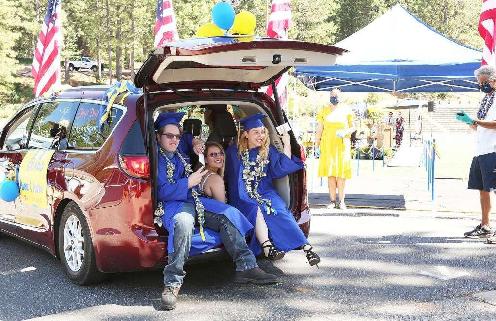 Nevada Union High School held the first of its two days of drive-thru graduations May 27 at Grass Valley's Hooper Stadium. Vehicles packed with family friends and graduates gathered at the high school during their allotted time before driving to the stadium where students, such as twins Amber and Austin Fackrell, walked across the stage to receive their diplomas. | Photo: Elias Funez