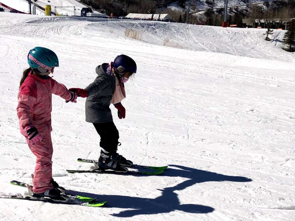 Eisley Ulibarry Hass (left) and Audrey Enriquez-Trujillo team up at Buttermilk on March 12, 2021 during a ski day program for third grade students at Glenwood Springs Elementary School, Kaya Williams / The Aspen Times