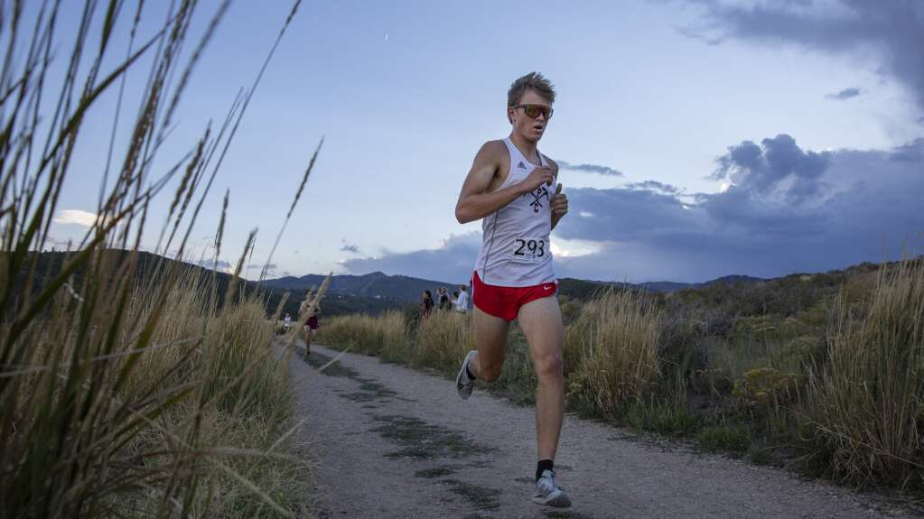 Park City High School's Wes Campbell picks up the pace as he approaches the final stretch of the course during the Park City Invitational cross-country meet in Round Valley Friday evening. Campbell finished in ninth place, and the boys team took second place overall. (Tanzi Propst/Park Record)