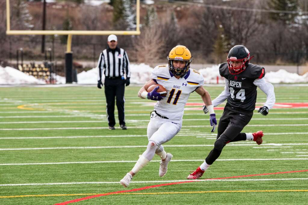 Basalt High School's running back Gavin Webb runs to the end zone as Aspen's Bodie Grogan pursues him during the game at Aspen on Friday, April 16, 2021. (Kelsey Brunner/The Aspen Times)