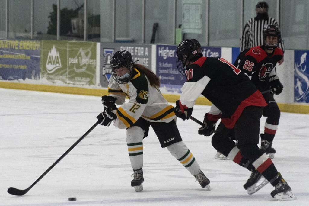 Summit High School's Peyton McGuan skates past a Glenwood Springs defender at Stephen C. West Ice Arena in Breckenridge on Tuesday, March 9. | Photo by Jason Connolly / Jason Connolly Photography