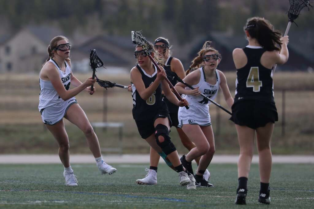 The Summit High School girls varsity lacrosse team defends in the season opener vs. Battle Mountain on May 8 in Breckenridge. | Photo by Ashley Low / Ashley Low Photography