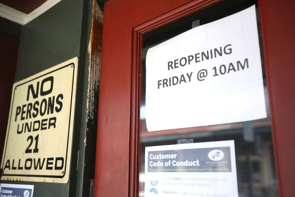 A sign on the door at the Nevada Club in downtown Grass Valley states that they will be reopening during the week of June 11. While many drinking establishments have been able to remain open with their food menus, bars such as the Nevada Club have remained closed since the coronavirus shutdowns were implemented mid March. | Photo: Elias Funez