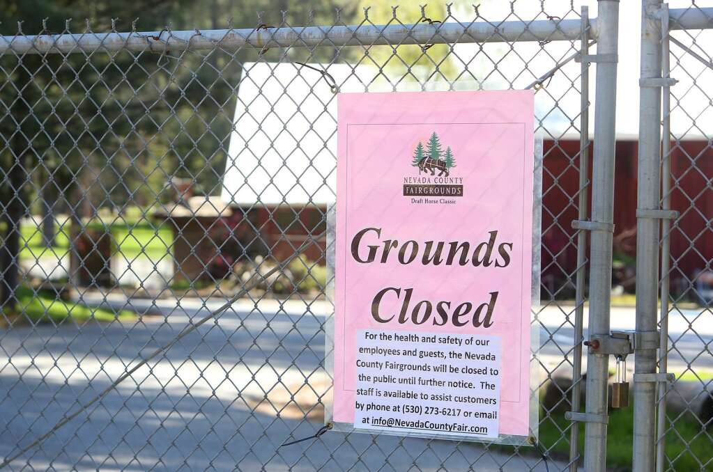 A locked chain link fence is accompanied with a sign instructing people how to get a hold of fairgrounds staff. | Photo: Elias Funez