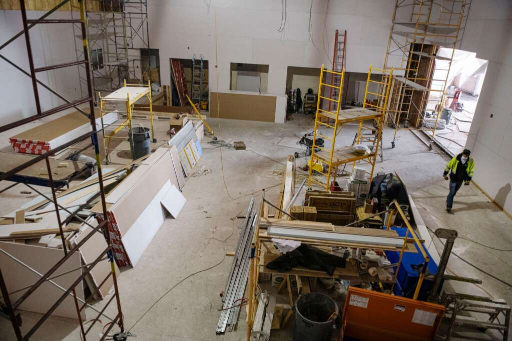 An electrician walks through the room with the main stage at the performing arts center being constructed by The Arts Campus at Willits in Basalt on Thursday, March 18, 2021. (Kelsey Brunner/The Aspen Times)