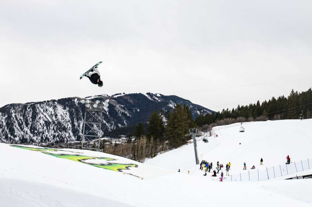 New Zealand snowboarder Zoi Sadowski-Synnott hits the fin feature during the womens snowboard slopestyle finals as a group of skiers watch the bottom of the course during the 2021 X Games Aspen at Buttermilk on Friday, Jan. 29, 2021. (Kelsey Brunner/The Aspen Times)