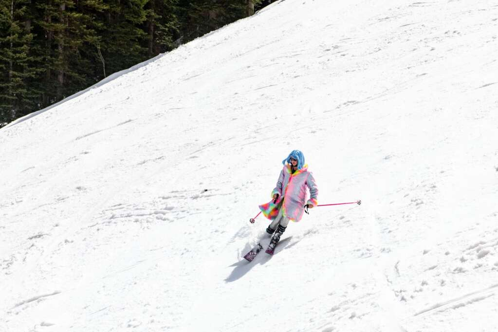 A skier maneuvers spring snow while dressed for Snowmass closing day while skiing under the Village Express Lift on Sunday, April 25, 2021. (Kelsey Brunner/The Aspen Times)