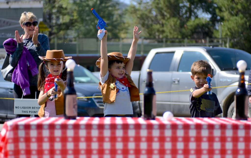 Macklin Pappas, center, celebrates after he shoots a ping pong ball of a rootbeer bottle with his water gun on Saturday in Grand Lake. Kinsley Pappas, left, and Eli Berg attempt to do the same.   Amy Golden / agolden@skyhinews.com