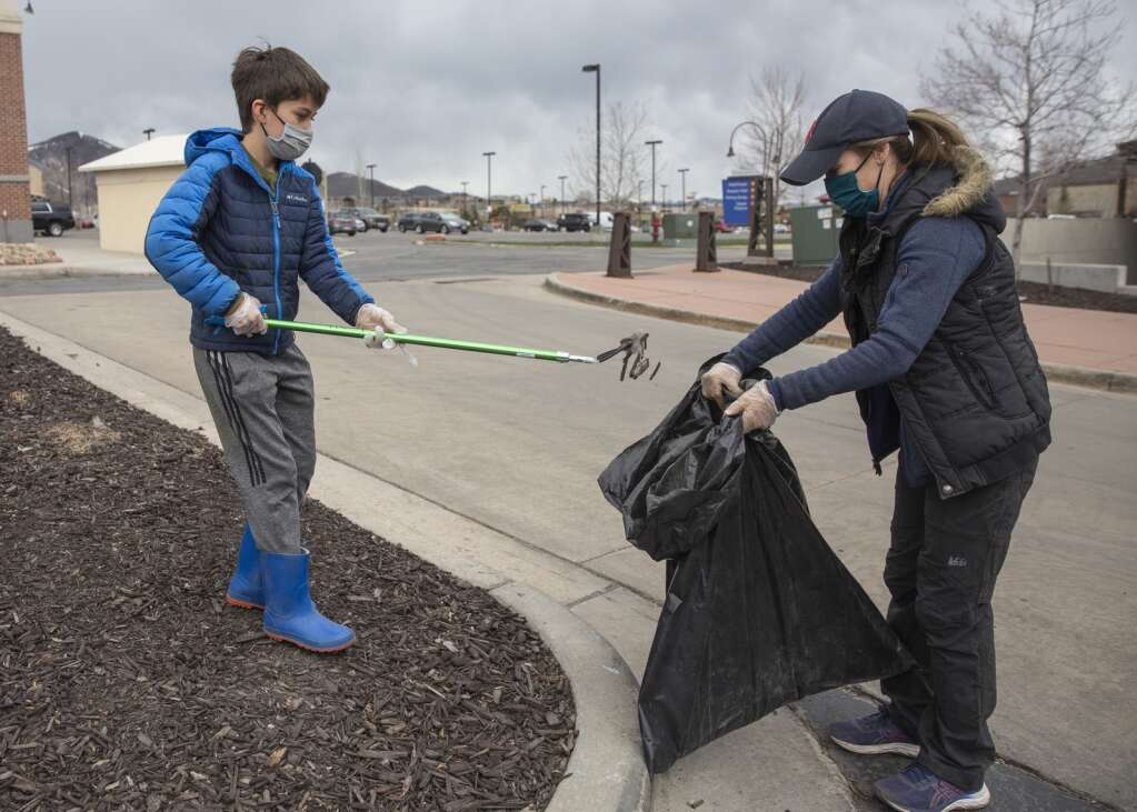 Nico Silvero, 10, left, and his mom Beth Silvero discard of litter found in the parking lot behind Storm Cycles and Best Buy in Newpark during a clean-up event hosted by the Swaner Preserve and EcoCenter on Saturday. The group picked up litter around many of the businesses in the area. (Tanzi Propst/Park Record)