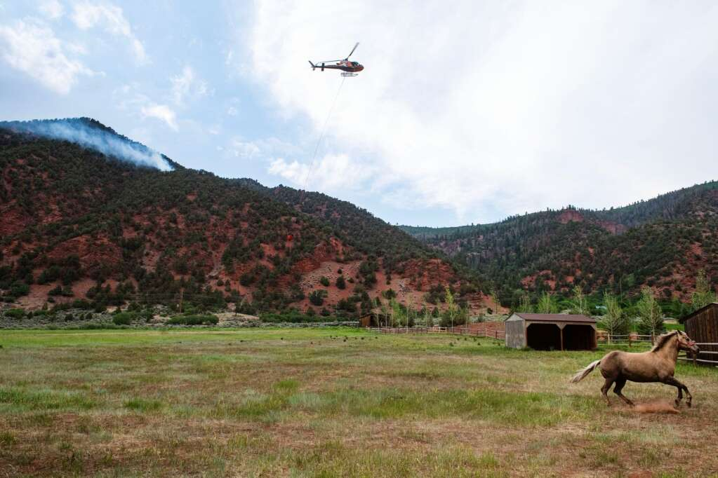 A horse gallops through a pasture as a helicopter refills with water for the fire burning above the property near Lower River Road in Old Snowmass on Friday, June 18, 2021. (Kelsey Brunner/The Aspen Times)