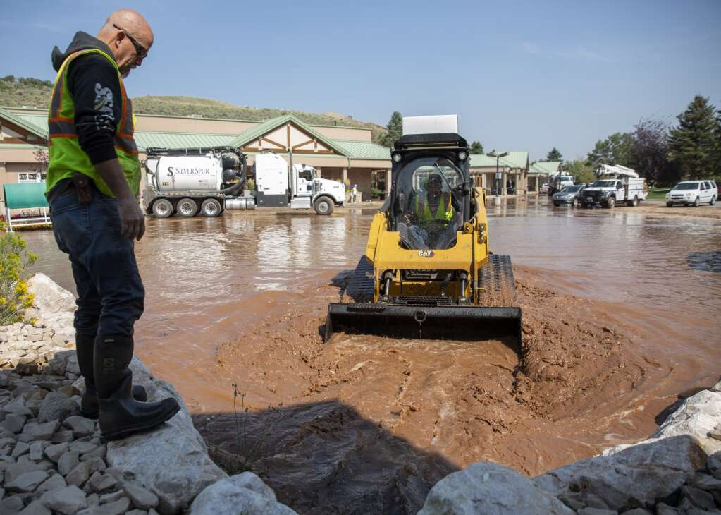 Justin Fratto, left, with Silver Spur Construction works to clear the parking lot drain of debris with a coworker. A water line break near Snow Creek Drive sent water flowing into the parking lots of the nearby business strip Tuesday afternoon, Sept. 6, 2021. (Tanzi Propst/Park Record)