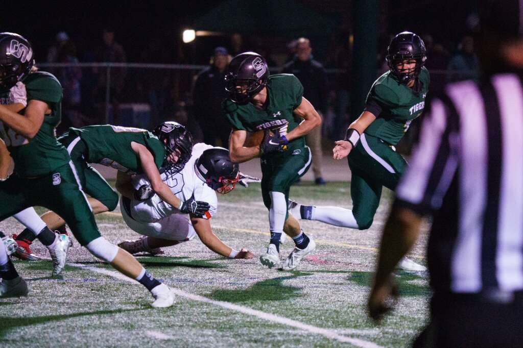 Summit Tigers junior quarterback Jack Schierholz hands the ball off to Aidan Collins resulting in the final touchdown for the Tigers in their 37-20 win over the Aspen Skiers Friday, Sept. 10, at Tiger Stadium in Breckenridge. | John Hanson/For the Summit Daily News