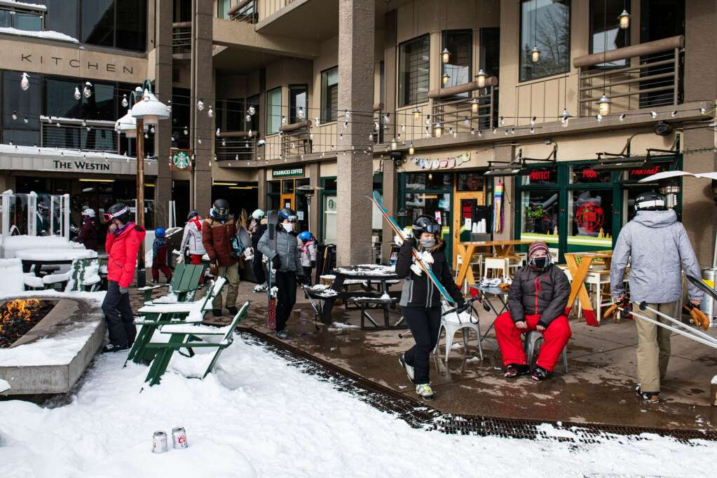 Skiers walk through the Snowmass Village Mall in front of the Snowmass Sports, Ranger Station and Starbucks on Tuesday, Dec. 29, 2020. (Kelsey Brunner/The Aspen Times)