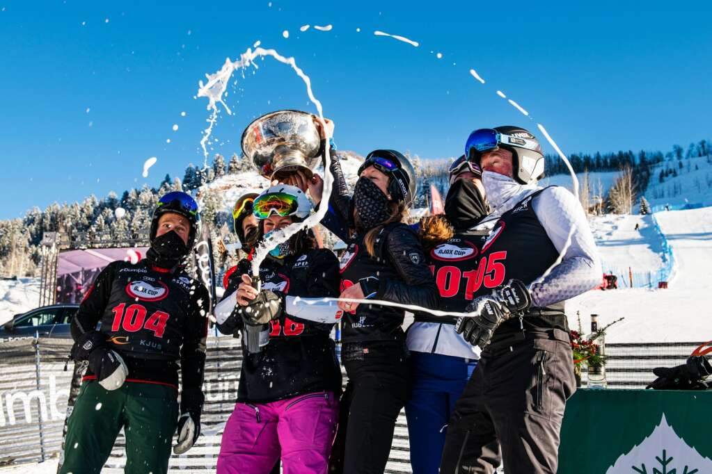 Kristina Koznick, center, sprays champagne with the winning team Independiente at the base of the Stapleton Training Center after the 2020 Ajax Cup at Aspen Highlands on Wednesday, Dec. 30, 2020. (Kelsey Brunner/The Aspen Times)