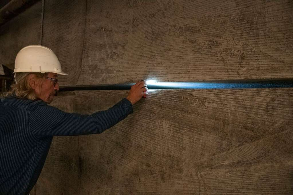 Robert Congdon lights up the slit between the wall at his Alabaster Mine outside of Redstone on Thursday, July 29, 2021. (Kelsey Brunner/The Aspen Times)