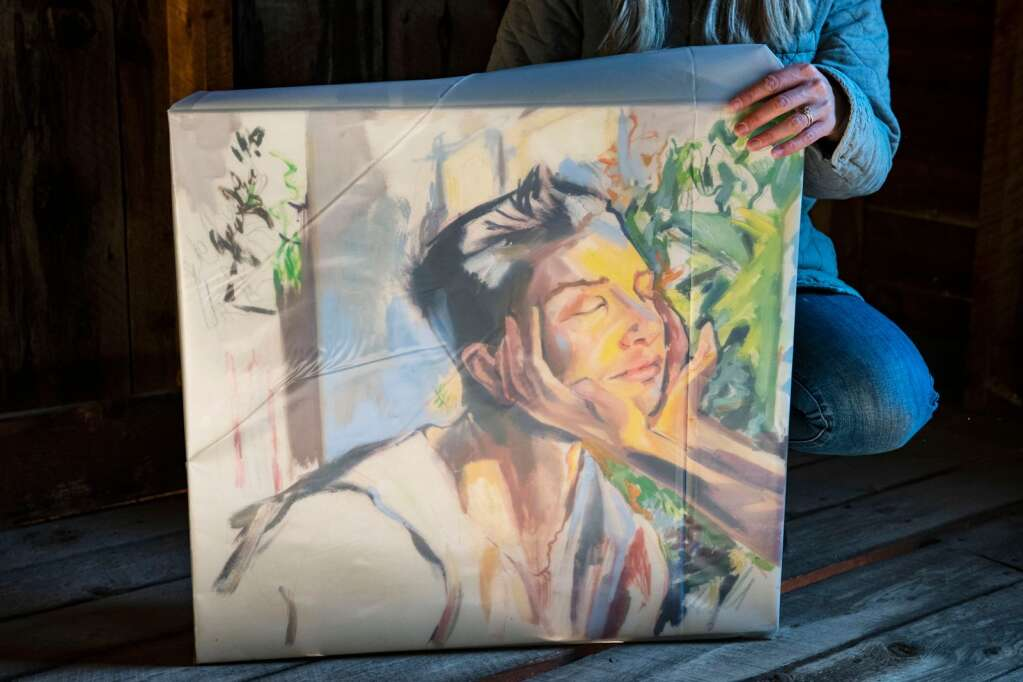 Denver-based artist Kaitlyn Tucek unwraps a painting in a building in the Ashcroft Ghost Town outside of Aspen as part of her two-day exhibition 'The Lilac Hour' outside of Aspen on Friday, Sept. 17, 2021. (Kelsey Brunner/The Aspen Times)