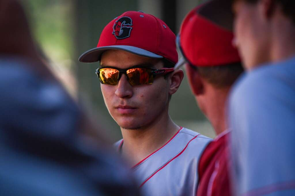 A Glenwood Springs Demon listens to head coach Eric Nieslanik in between innings during Monday's game against the Rifle Bears. |Chelsea Self / Post Independent