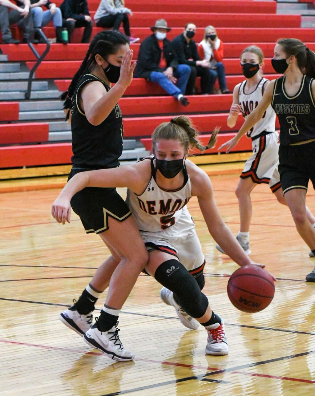 Glenwood Springs Demon Kenzie Winder dribbles the ball around the defending Battle Mountain Husky during Thursday night's game at Glenwood Springs High School. |Chelsea Self / Post Independent