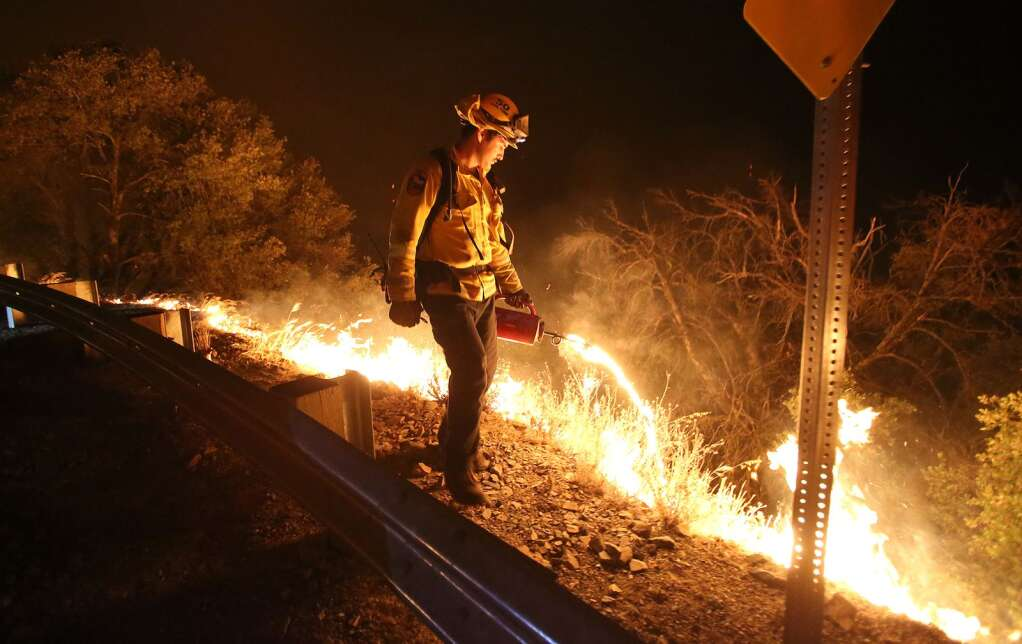 A Cal Fire firefighter initiates a firing procedure where fire fuel is ignited to back burn vegetation down the Yuba River Canyon towards the flames of the Jones Fire Tuesday morning. | Photo: Elias Funez