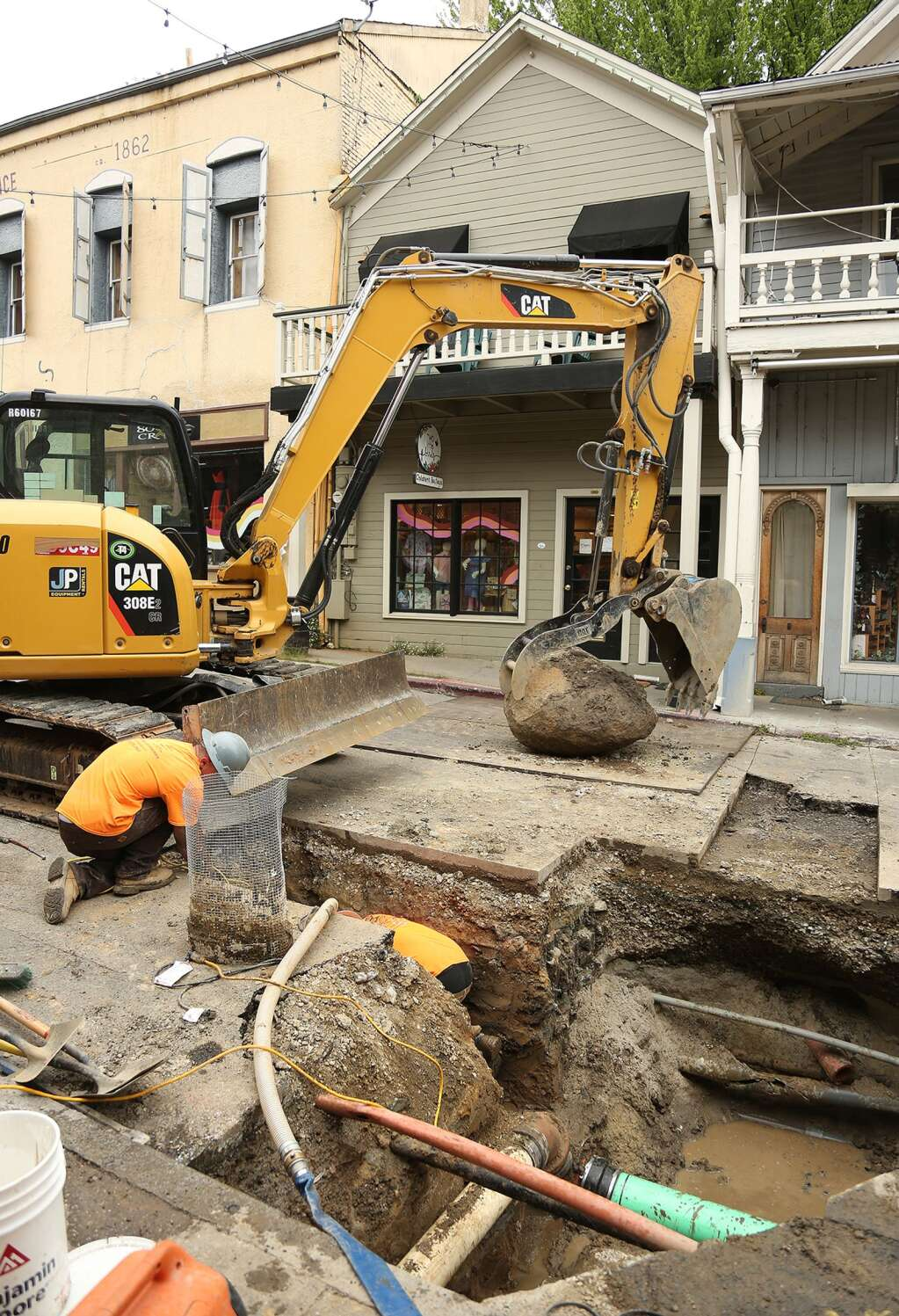 A large boulder was pulled from the middle of commercial street in Nevada City which was causing trouble for workers replacing sewer mains March 13. | Photo: Elias Funez