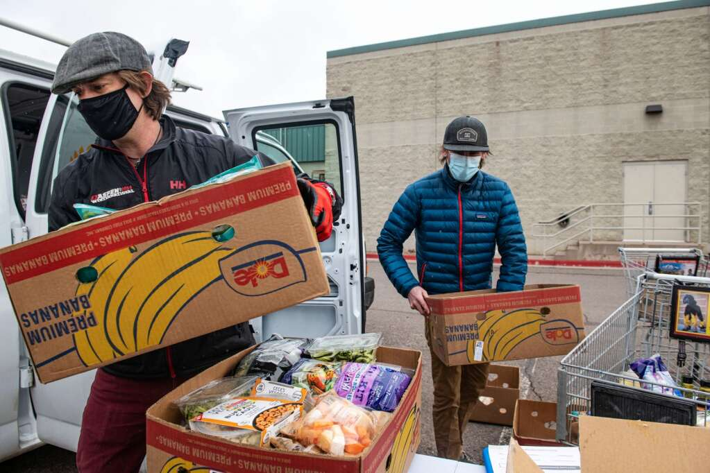 Harvest for Hunger's founder and executive director Gray Warr and board of directors member Matt Hooks load the van with pounds of food from City Market in El Jebel on Tuesday, March 23, 2021. (Kelsey Brunner/The Aspen Times)