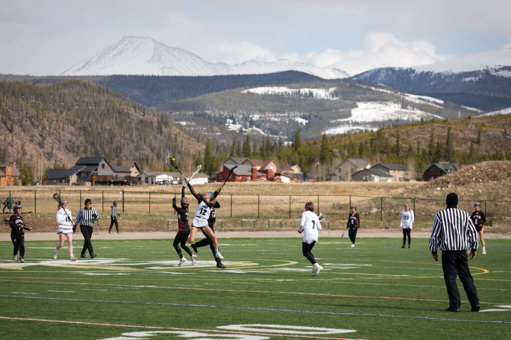 Katherine Costello cradles a loose ball during the Summit High School varsity girls lacrosse team's 14-4 loss to Eagle Valley at Summit High School in Breckenridge on Tuesday, May 11, 2021. | Photo by Lucas Herbert / Lucas Herbert Media