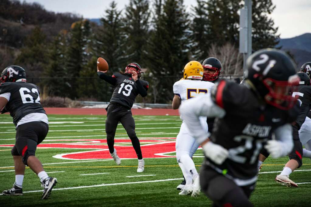 Aspen High School's quarterback Nate Thomas looks to pass to wide receiver Noah Akin during the senior night game against Basalt High School on Friday, April 16, 2021. (Kelsey Brunner/The Aspen Times)