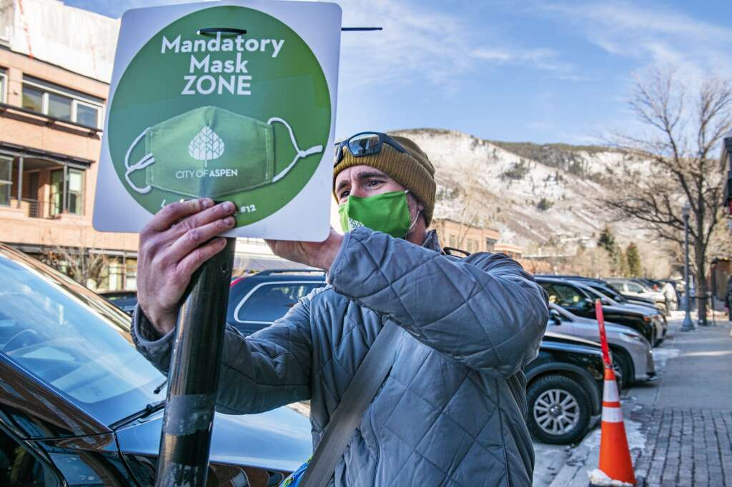 City of Aspen consumer health protection specialist Mike Sear checks the mask zone sign on a parking department pole in downtown Aspen on Friday, Jan. 15, 2021. The hope is to remove all of the mask zone signs on the sidewalk as they're now getting ruined during the winter. (Kelsey Brunner/The Aspen Times)