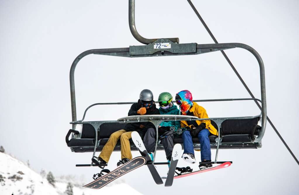 A skier and a snowboarder ride the Village Express Lift on Snowmass on Tuesday, Dec. 29, 2020. (Kelsey Brunner/The Aspen Times)